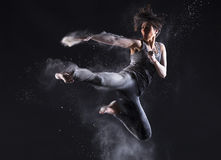 Female Martial Artist with Powder Jump Kick. Female martial artist with back lit powder showing explosive power and technique over black background.  Flying side Stock Image