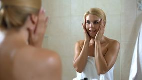 Female massaging and creaming face with moisturizing lotion, home spa treatment stock images