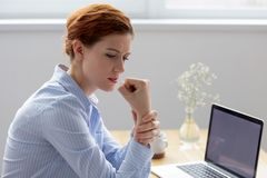 Female massaging wrist having carpal tunnel syndrome. Businesswoman sitting at desk opposite pc suffers from pain in hand while working in office. Young female stock photo