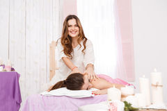 Female masseur doing massage on woman back at day spa. Masseur doing massage on women back at day spa smiling cheerfully, working in bright room Stock Image