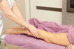 Female masseuse doing legs massage Royalty Free Stock Photos