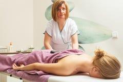 Female masseuse doing massage with hot stones Stock Photo