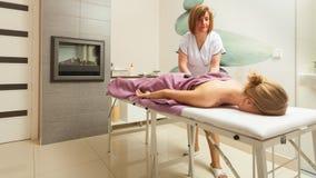 Female masseuse doing massage with hot stones Royalty Free Stock Photos
