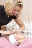 Female masseuse giving client facial Stock Photos