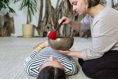 Free Female Masseuse Perform Traditional Tibetan Sound Therapy, Singing Bowls Massage At Relaxed Woman Royalty Free Stock Photo - 218320465
