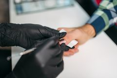 Master in gloves polishing nails to male client royalty free stock photography