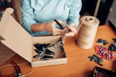 Female master with scissors makes handmade earring. Needlework, bijouterie making process Stock Photo