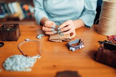 Female master with scissors makes handmade earring. Needlework, bijouterie making process Stock Photos