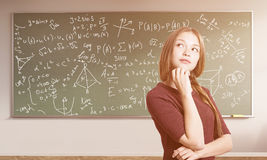 Female math genius portrait. Portrait of young woman with braided hair standing near green chalkboard with formulas in a classroom. Concept of exact sciences royalty free stock images