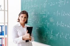 The female math teacher in front of the chalkboard. Female math teacher in front of the chalkboard stock photography