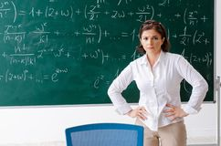 The female math teacher in front of the chalkboard. Female math teacher in front of the chalkboard royalty free stock photos