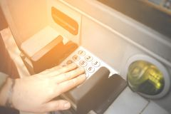 Female mature entering PIN numbers on ATM bank machine . Concept of insecure strangers , thugs , thieves  online payments  , robbe. Ry and scam  . Hand royalty free stock images