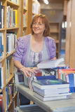 Female mature librarian returning books in library. Smiling at camera Royalty Free Stock Photos