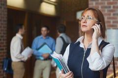 Female mature student phoning standing in corridor Stock Image