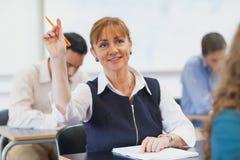 Female mature student raising her hand Royalty Free Stock Image