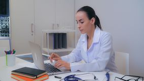 Female md surfing internet on laptop in clinic. royalty free stock images