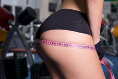 Female measuring buttocks. Female measuring ass with measurement tape in gym Royalty Free Stock Photo