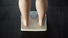 Female measuring weight on bathroom scales, word normal on screen, rear view royalty free stock images