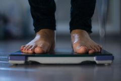 Female measuring weight on health scale. Close-up. Woman legs approaching to weighing digital instrument royalty free stock images