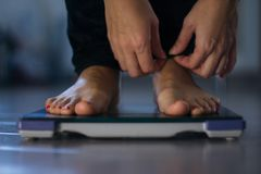 Female measuring weight on health scale. Close-up. Woman legs approaching to weighing digital instrument royalty free stock photo