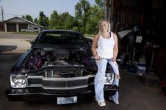 Female Mechanic. A female mechanic sitting on a car stock photo