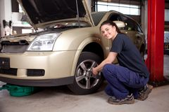 Female Mechanic. Beautiful female mechanic changing tire on car royalty free stock images