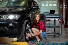 Female mechanic changing tire with air impact wrench Stock Photo