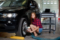 Female mechanic changing tire with air impact wrench. Young sexy woman in checked shirt Royalty Free Stock Images