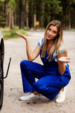 Female mechanic changing tire with wheel wrench Royalty Free Stock Photos