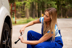 Female mechanic changing tire with wheel wrench Stock Photos