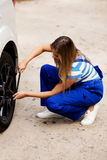 Female mechanic changing tire with wheel wrench Stock Photo