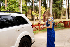 Female mechanic changing tire with wheel wrench Stock Image