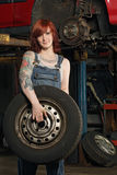 Female mechanic changing tires Royalty Free Stock Photography