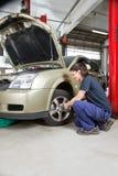 Female mechanic changing wheel Royalty Free Stock Photography