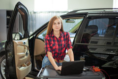 Female mechanic in checked shirt at work. auto service station. Royalty Free Stock Image