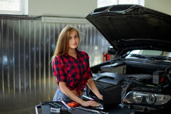 Female mechanic in checked shirt at work. auto service station. Stock Photography