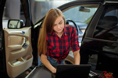 Female mechanic in checked shirt at work. auto service station. Stock Photos