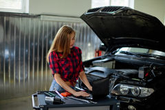 Female mechanic in checked shirt at work. auto service station. Stock Images