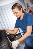 Female Mechanic Examining Car Tire stock photography