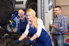 Female mechanic is fixing a car Royalty Free Stock Image