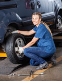 Female Mechanic Fixing Car Tire Royalty Free Stock Photos