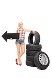 Female mechanic holding a an arrow pointing left. Full length portrait of a female mechanic holding a big black arrow pointing left and leaning on a stack of car stock photo