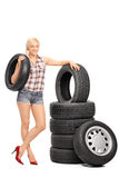 Female mechanic holding a car tire. Full length portrait of a female mechanic holding a car tire and standing next to a stack of tires isolated on white Royalty Free Stock Photos