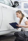 Female mechanic holding clipboard while examining car body at repair shop Stock Photo