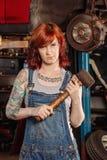 Female mechanic holding rubber mallet stock photo