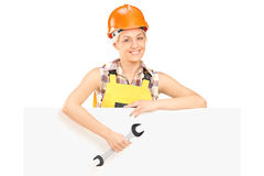 Female mechanic holding wrench behind a panel Royalty Free Stock Images