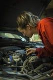 Female mechanic inspecting car engine. Female mechanic inspecting a car engine close-up Royalty Free Stock Photography
