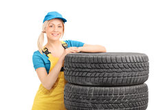 Female mechanic leaning on a stack of used tires Royalty Free Stock Photo