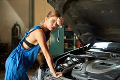 Female mechanic leans on the car with a wrench in her hands stock photography