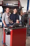 Female Mechanic with Male Customer. Woman mechanic going over work order on laptop with customer man Stock Photos